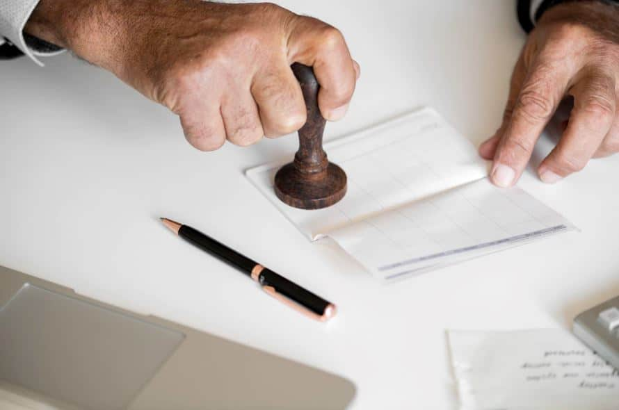 Accountant balancing and approving charges in a checkbook.