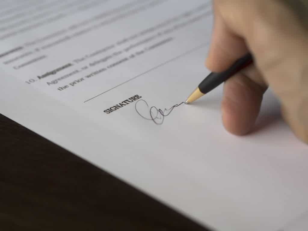 A businessman signs a letter of intent, which is an important part of an acquisition strategy
