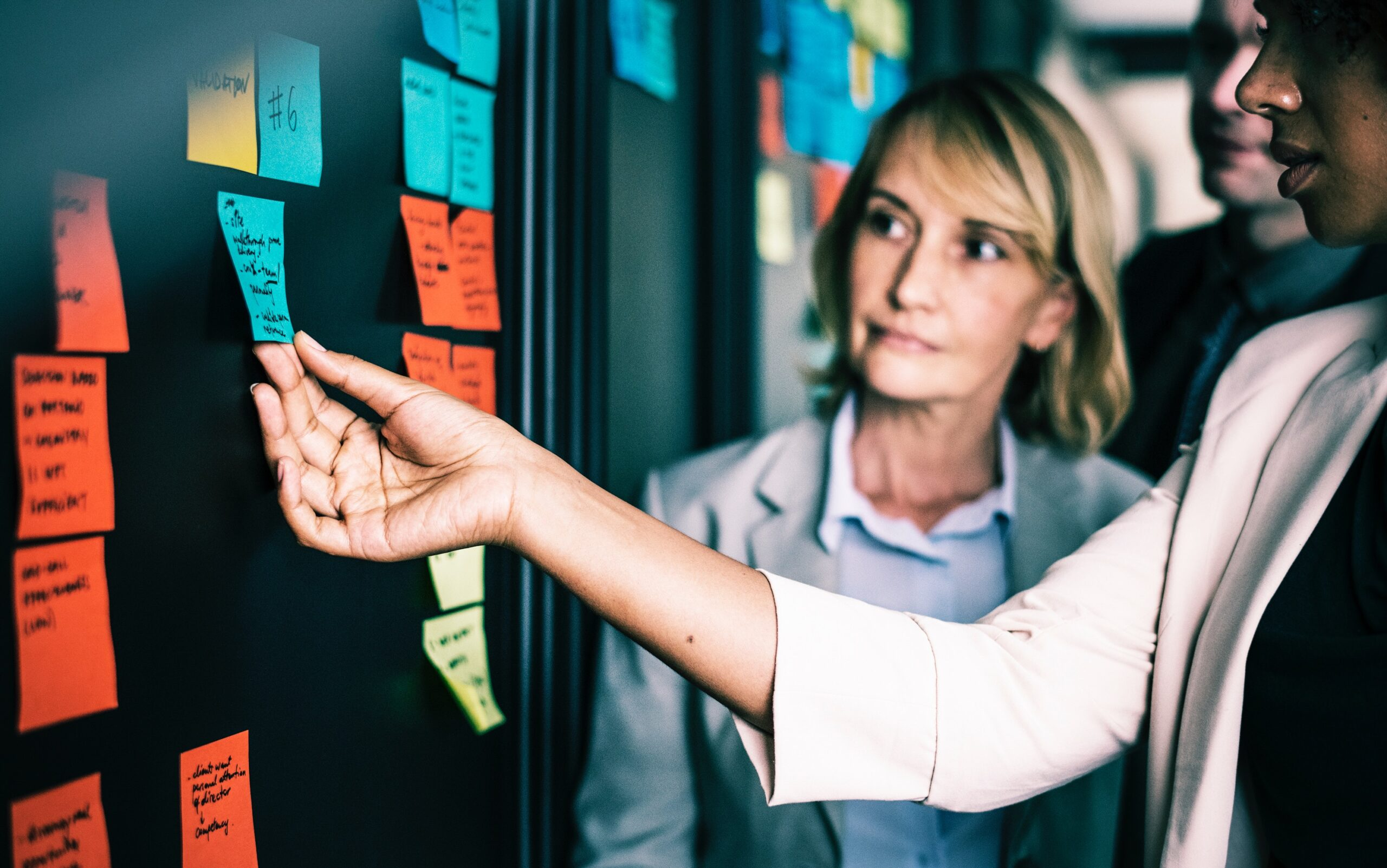 Two women delegating tasks on post it notes on an ideas board in an office space.