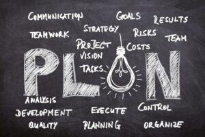 PLAN written on a blackboard with communication, teamwork, strategy, goals, planning, development, problems written around it